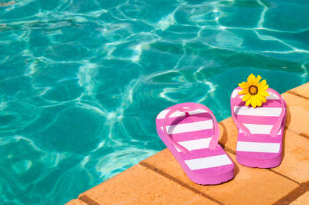 flip flops: Colorful summer flip flops by the side of luxury swimming pool with flower Stock Photo