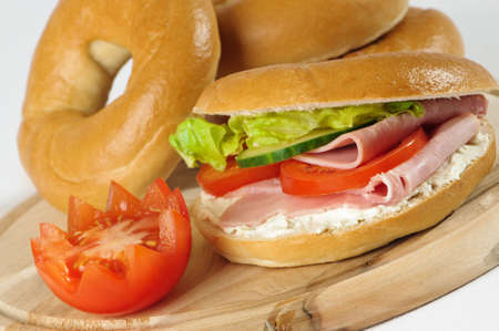 Close up of bagels on rustic wooden board with tomato garnish Stock Photo - 5084498