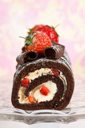 Christmas yule log decorated with chocolate curls and strawberries on glass comport Stock Photo - 5084512