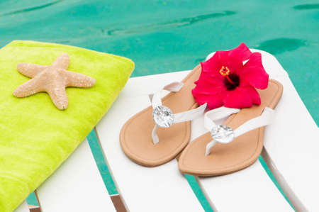 flip flops: Sandals and beach towel on sunbed at the side of the swimming pool