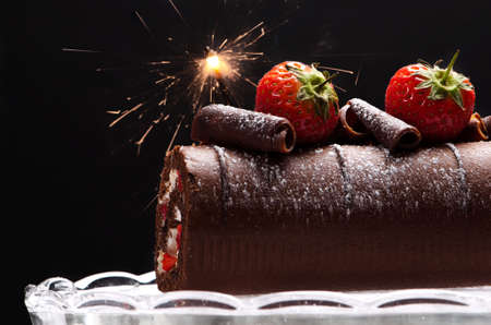 Chocolate swiss roll with strawberries and sparkler decoration photo