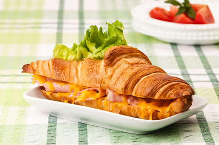 Ham and melted cheese croissant on table with tomato garnish in background photo