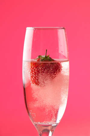 Champagne bubbles with strawberry, pink background photo