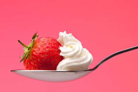 Spoon of fresh strawberry and cream on pink background