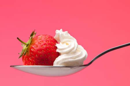 cream colour: Un cucchiaio di panna fresca fragola e rosa su sfondo