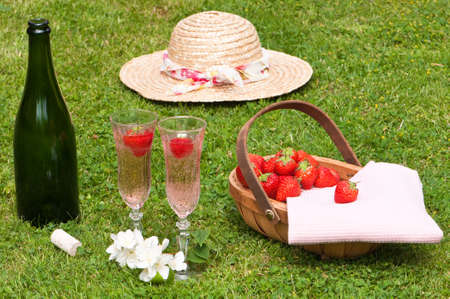 Strawberry and champagne picnic with basket of fruit photo