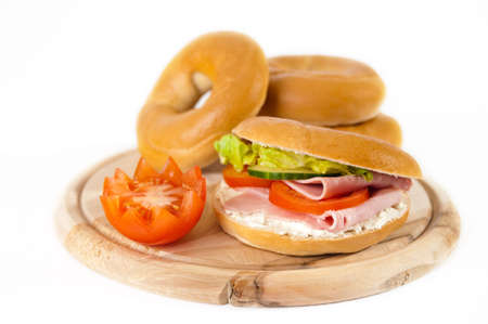 Lunchtime bagels filled with ham and cream cheese on wooden board with tomato garnish Stock Photo - 5099188