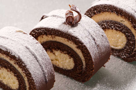 icing sugar: Slices of swiss roll chocolate cake on frosted glass plate
