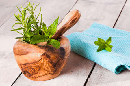 Herbs in mortar with pestle and teatowel on rustic table photo