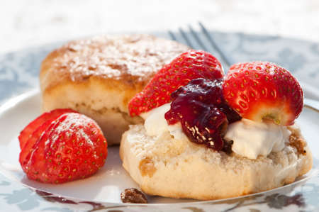 Plate of strawberry scones with clotted cream and jam photo
