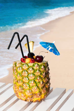 Fruity pineapple cocktail at the beach overlooking the ocean photo