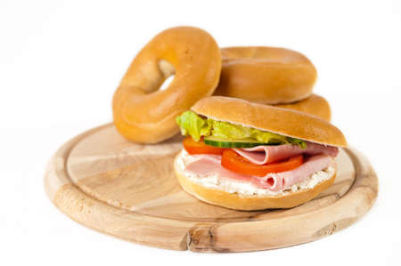 Ham & cream cheese bagels on wooden board, white background