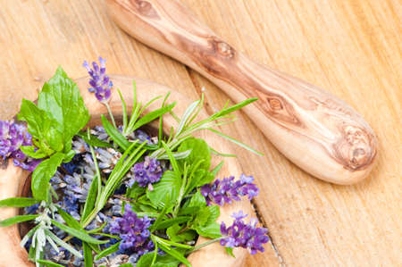 holistic view: Herbs and lavender in mortar with pestle on rustic table