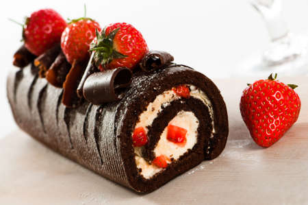 icing sugar: Chocolate swiss roll cake with strawberries