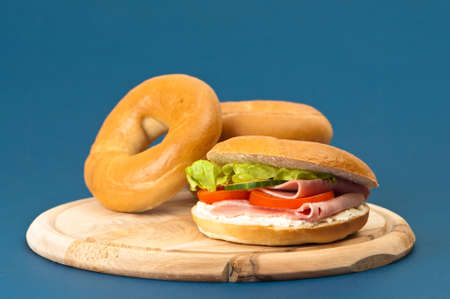 Fresh bagels filled with cream cheese and ham salad on blue background Stock Photo - 5234553