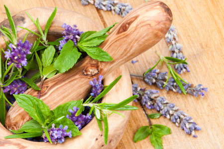 holistic view: Herbs and lavender with pestle and mortar on natural pine table Stock Photo