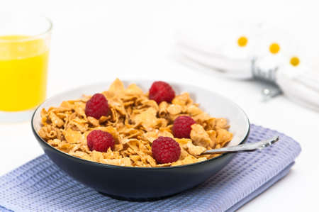 Healthy breakfast with cereal and raspberries, orange juice and napkin in background photo
