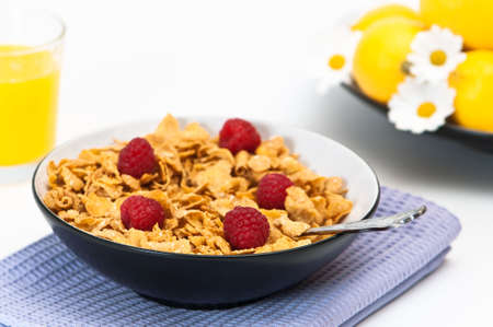 Breakfast cereal with raspberries and a glass of orange juice photo