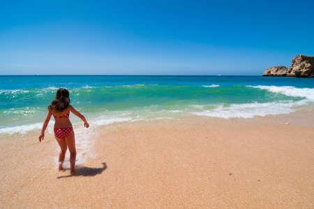 Woman in red polka dot bikini running into the ocean Stock Photo - 5315402