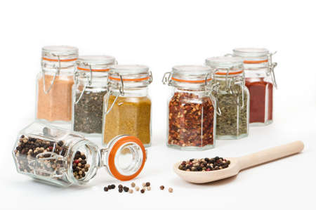 peppercorns: Spoonful of tropical peppercorns and filled spice jars