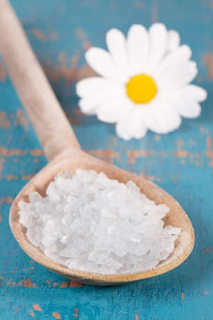 spoonful: Spoonful of sea salt crystals on wooden spoon with daisy in background