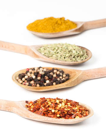 Row of colorful spices on rustic wooden spoons Stock Photo - 5378147