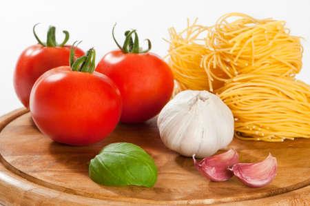 Italian pasta ingredients on rustic wooden board photo