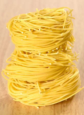 Vermicelli pasta nests stacked on wooden table  photo