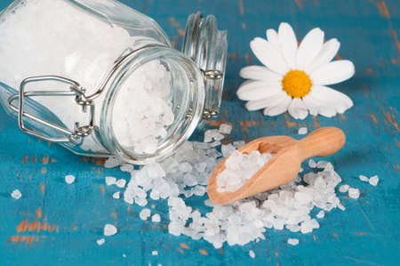Spice jar with rock salt crystals spilling onto rustic table with wooden scoop photo
