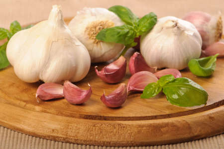 Garlic bulbs and cloves with basil on wooden chopping board photo