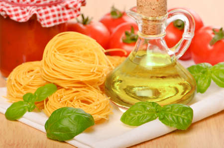 Vermicelli pasta with olive oil, tomato sauce and basil herbs on white cloth photo