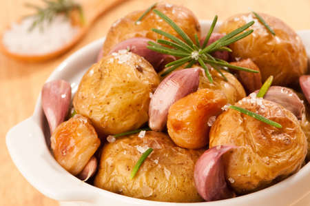 Close up of prepared potatoes with sea salt, garlic and rosemary with spoonful of salt in background photo