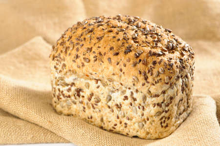 unsliced: Loaf of wholemeal bread with sunflower seeds on burlap cloth