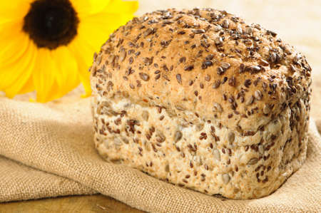 unsliced: Freshly baked loaf of bread with sunflower in background