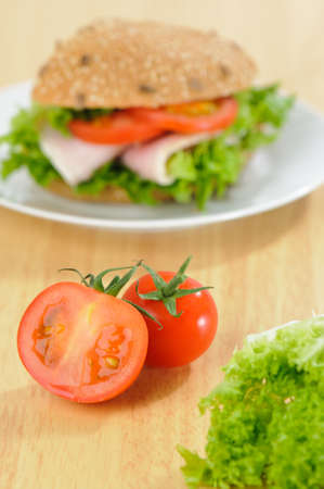 Vine tomatoes and lettuce with ham salad sandwich in background on pine table Stock Photo - 5465355