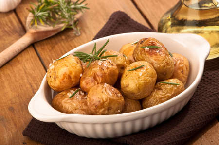 Roasted potatoes with sea salt and rosemary on rustic table photo