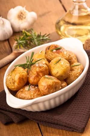 Roasted potatoes with rosemary herb with garlic and olive oil in background photo