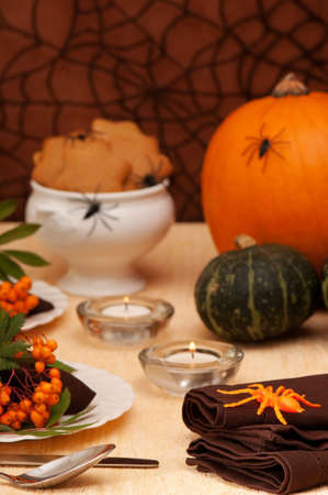 Halloween table setting with pumpkins and lit candles photo