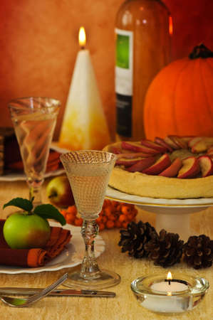 Thanksgiving harvest table setting with apple pie and pumpkin with wine photo