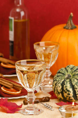 Thanksgiving table setting with white wine decorated with autumn leaves and pumpkin photo