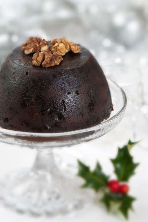 Christmas pudding topped with walnuts on glass comport photo