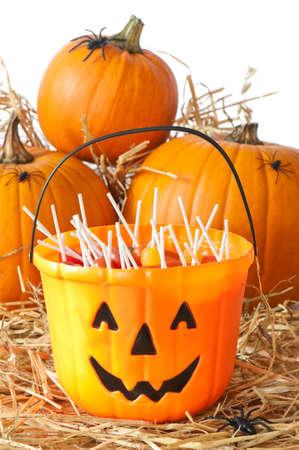 Halloween bucket filled with candies with orange pumpkins - white background photo