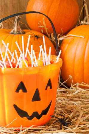 Trick or treat Halloween candies in the barn with orange pumpkins photo