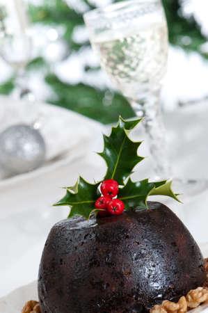 pudin: Close up of Christmas pudding con copas de Champa�a en segundo plano