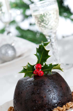Close up of Christmas pudding with glasses of champagne in background photo