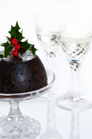 Christmas pudding decorated with holly and berries with glasses of champagne with high key lighting photo