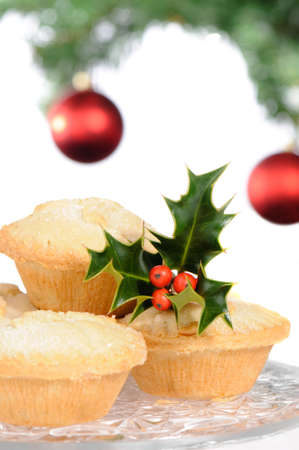 mince: Christmas mince pies with holly and berries with decorated tree in background