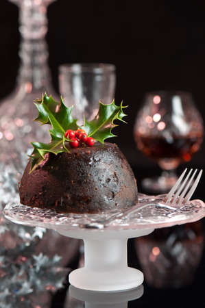 Festive Christmas pudding on comport decorated with holly and berries