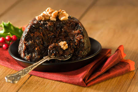 pudding: Spoonful of Christmas pudding decorated with walnuts in rustic setting