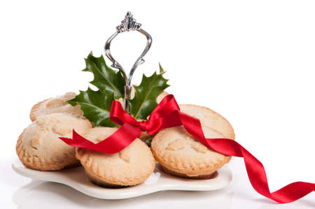 mince: Freshly baked traditional mince pies for Christmas on cake plate with holly and red ribbon bow Stock Photo